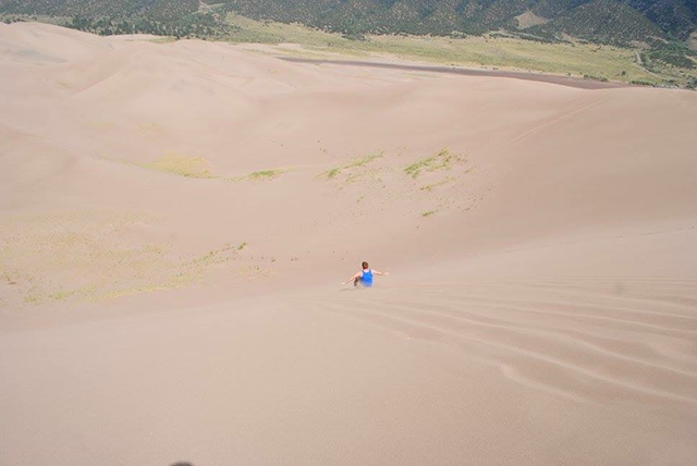 Having fun sledding down the dunes during a trip to Great Sand Dunes National Park.