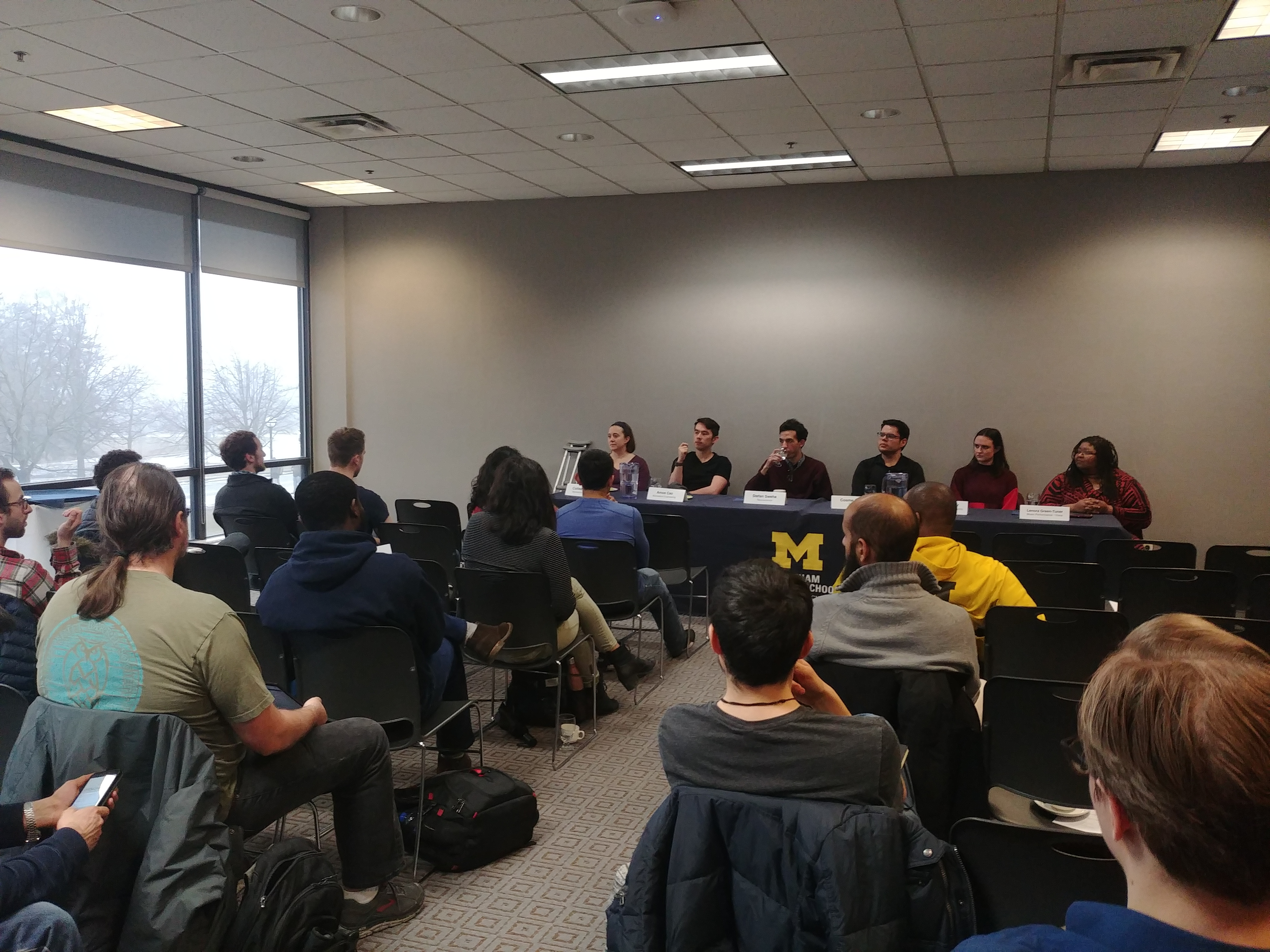 a classroom setting with a panel of speakers and students