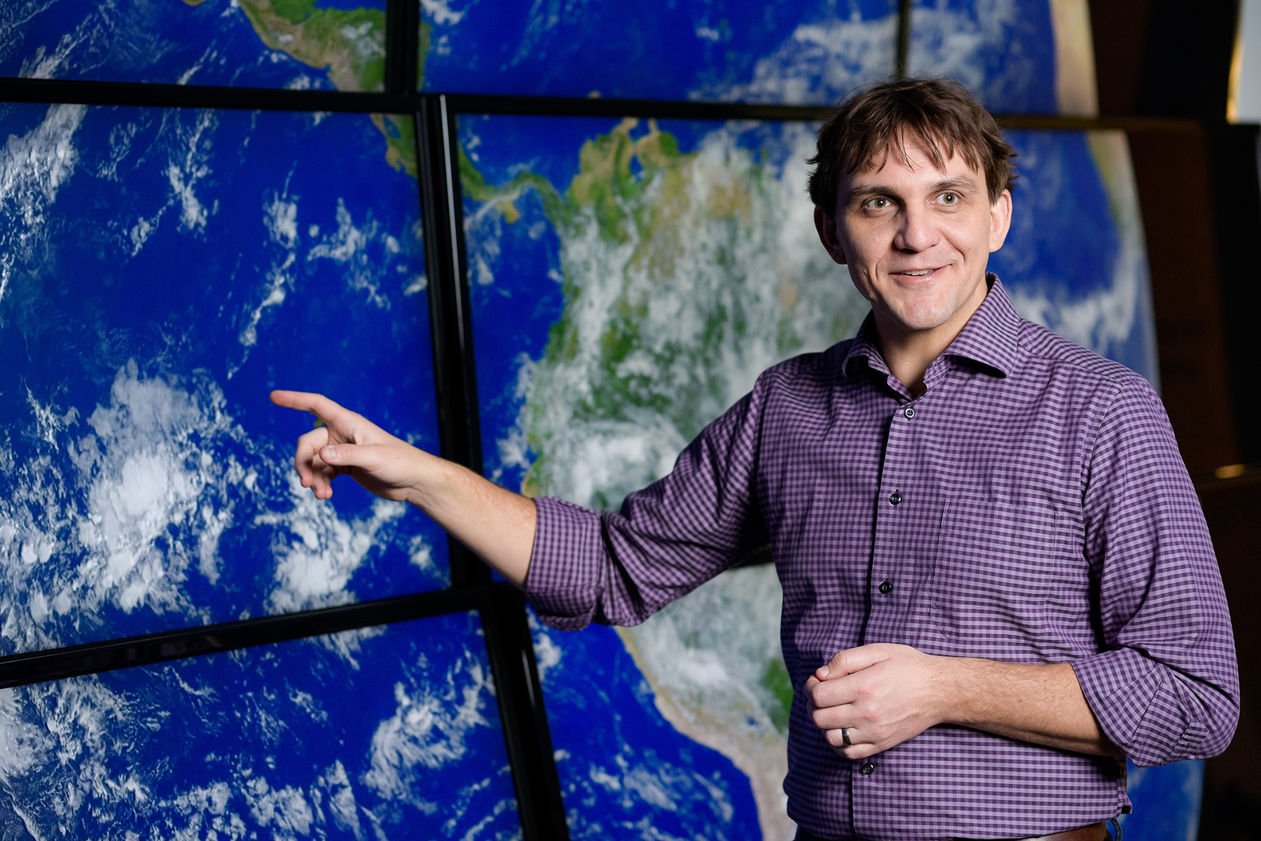 Daniel Horton in front of a world map.