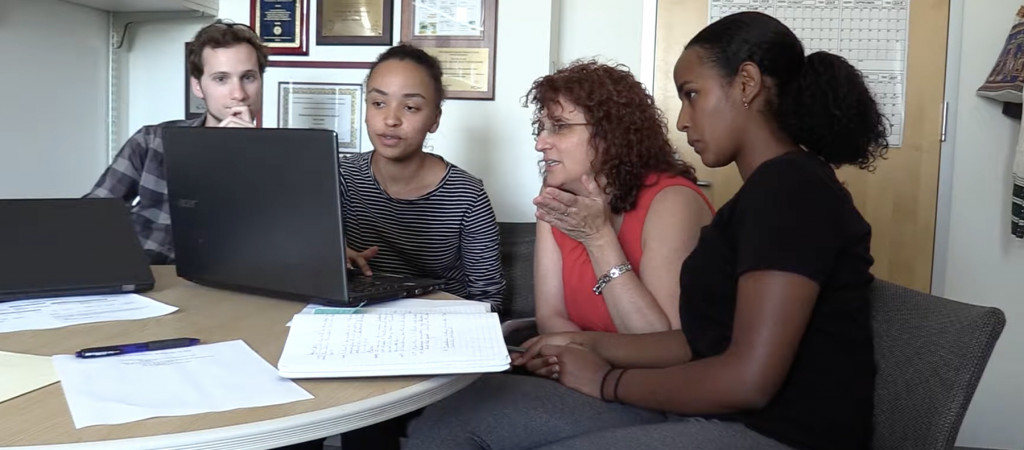 Associate dean Valeria Bertacco (second from right) works with students in the AURA program in a small group.