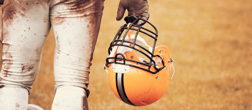 A hand holding a football helmet.