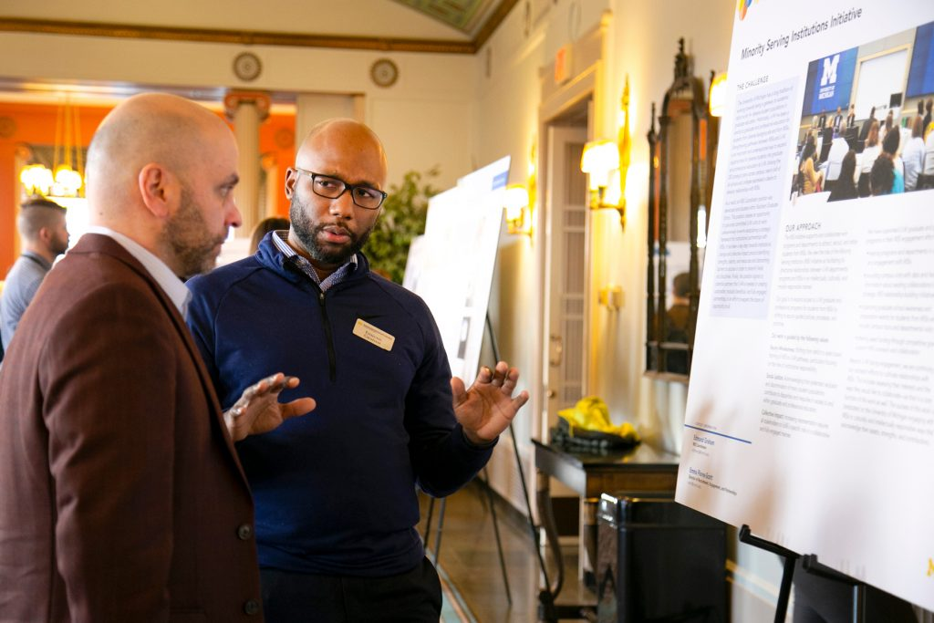 "Two men in conversations in front of a poster labeled ""Minority Serving Institutions Initiative."""