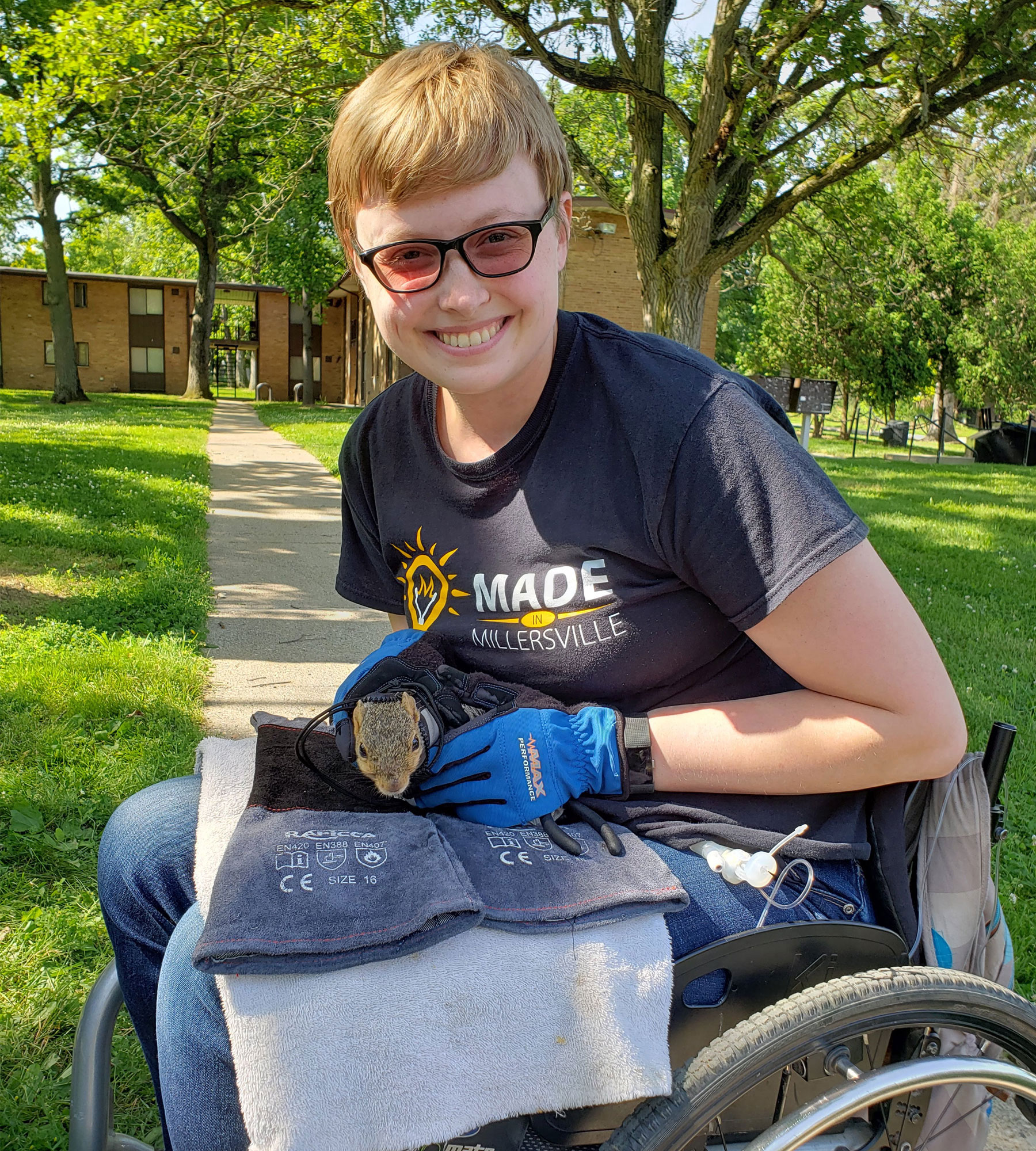 Amy-Charlotte Devitz sits in her motorized wheelchair and holds a squirrel during her on-campus research.