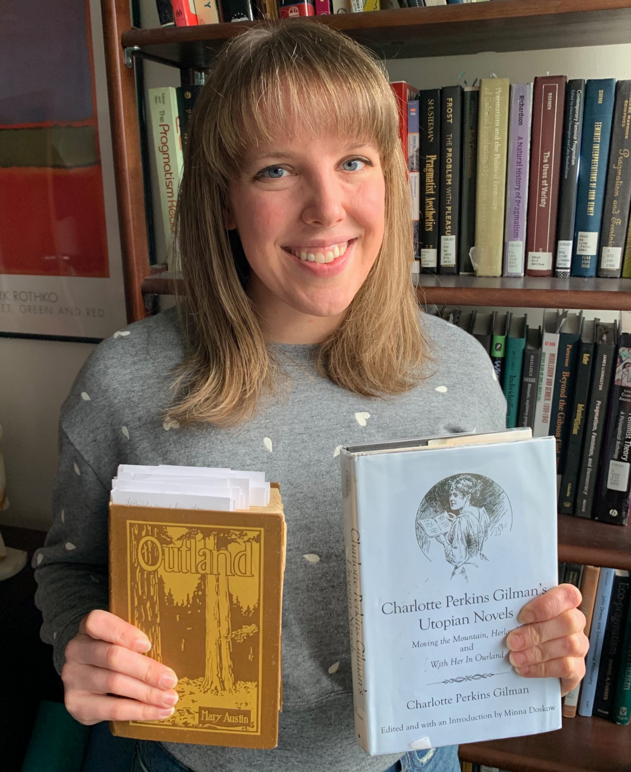 Elizabeth Harlow in front of a bookshelf, holding up copies of Mary Austin's Outland and the collected Utopian novels of Charlotte Perkins Gilman.