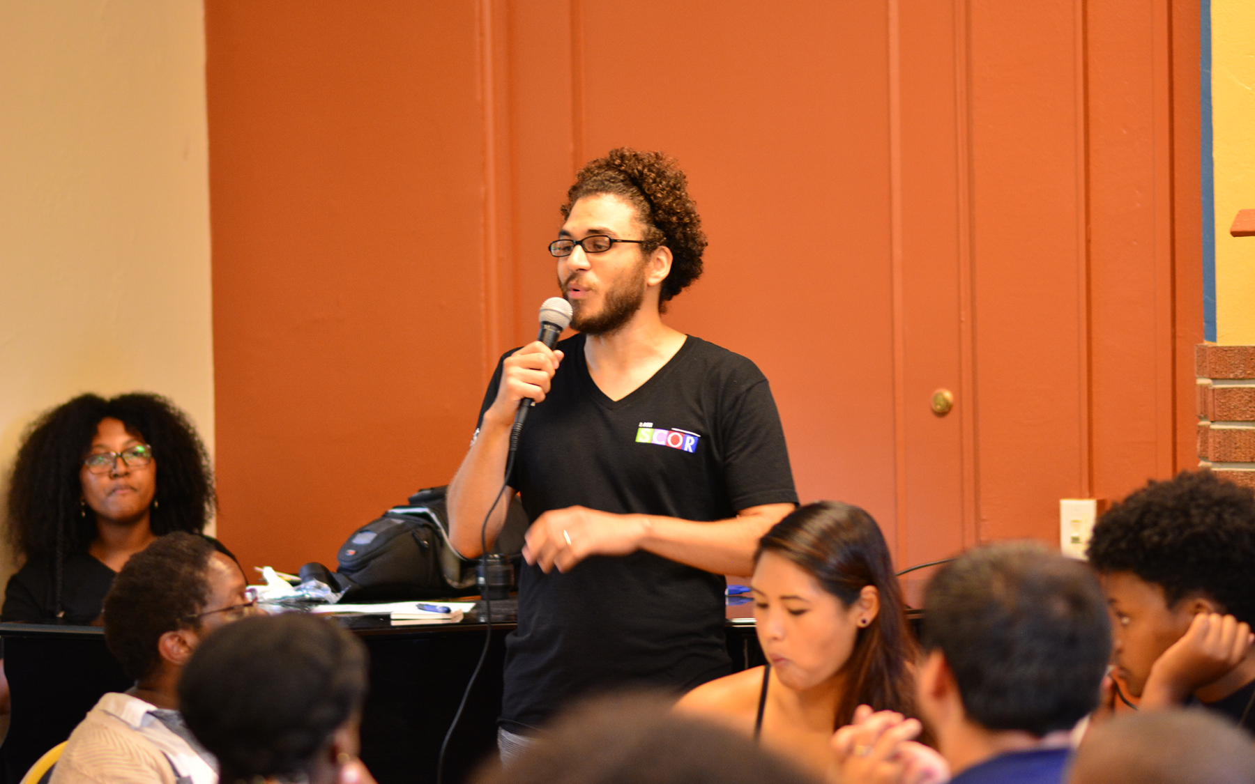 A SCOR member holding a microphone delivers remarks at an event.