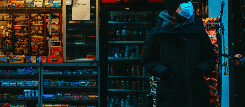 A person in a mask standing in a darkened convenience store.
