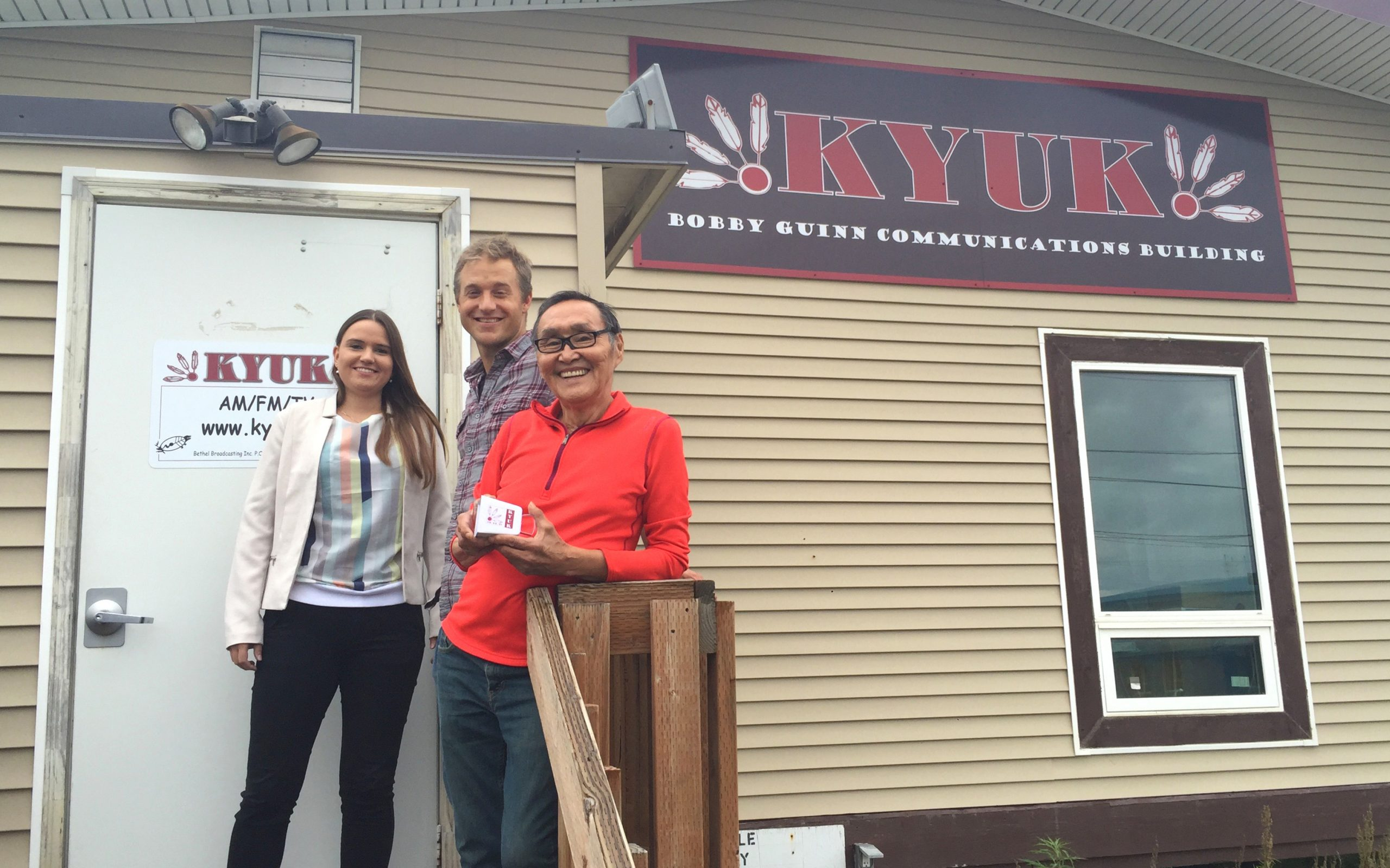 Three people standing in front of the KYUK radio station building.