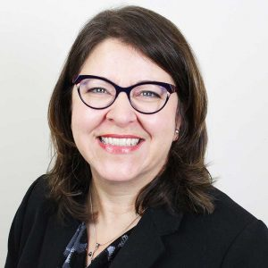 Melanie Sinche smiles for the camera, she's wearing a black blazer with coordinating blouse, she has shoulder-length brown hair, blue eyes, and wears glasses