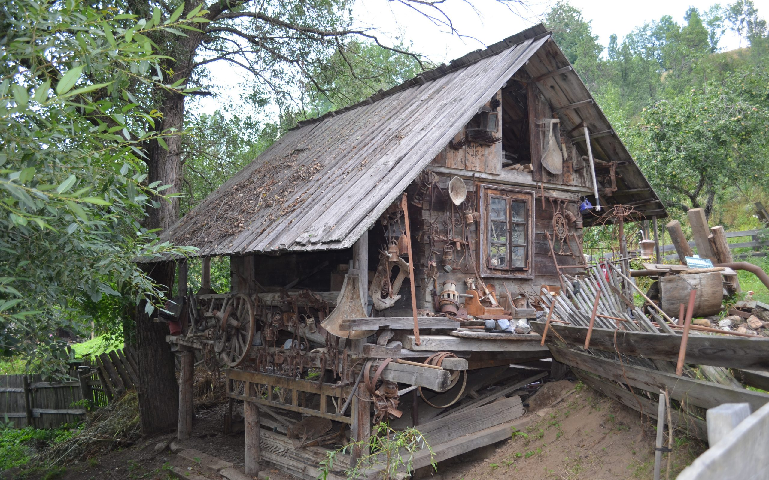 An old wooden building covered in mining tools.
