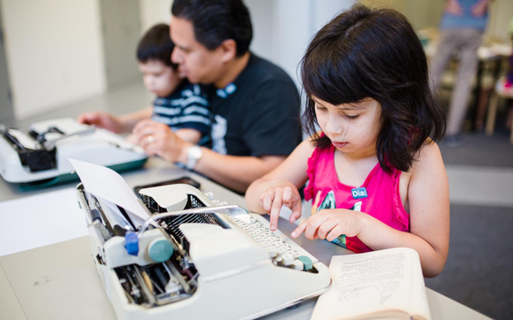 Children sitting at typewriters.
